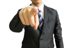 指をさして指摘する男性