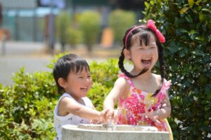 笑顔で水遊びをする男の子と女の子