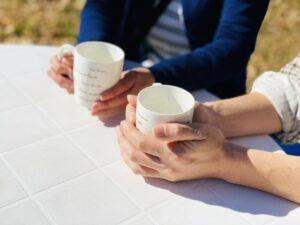 外のカフェでお茶を飲む男女