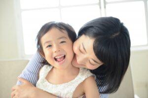 笑顔で子どもを抱く保育士