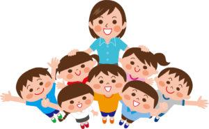 笑顔の子供たちに囲まれる保育士