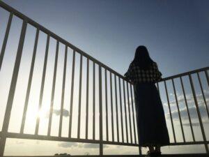 空を見て悩む女性