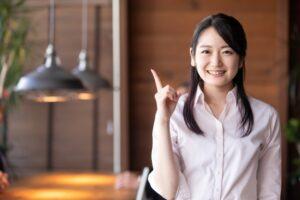 人差し指をたて微笑む女性