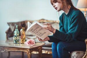 子供が嫌いになる原因を本を読んで考える女性