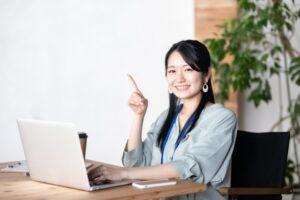 パソコンの前で人差し指を立てる女性