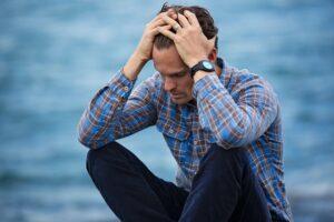 悩み頭を抱える男性